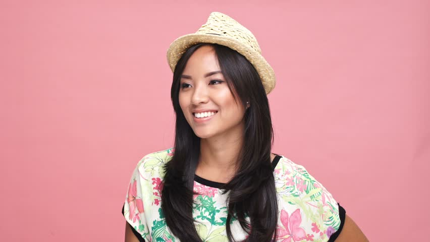 Young beautiful asian woman wearing hat wink over pink background