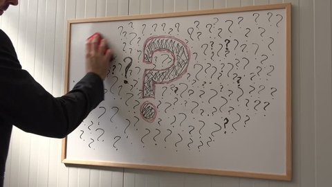 Businessman erasing question marks on office whiteboard during business seminar presentation, leaving one large symbol for big question