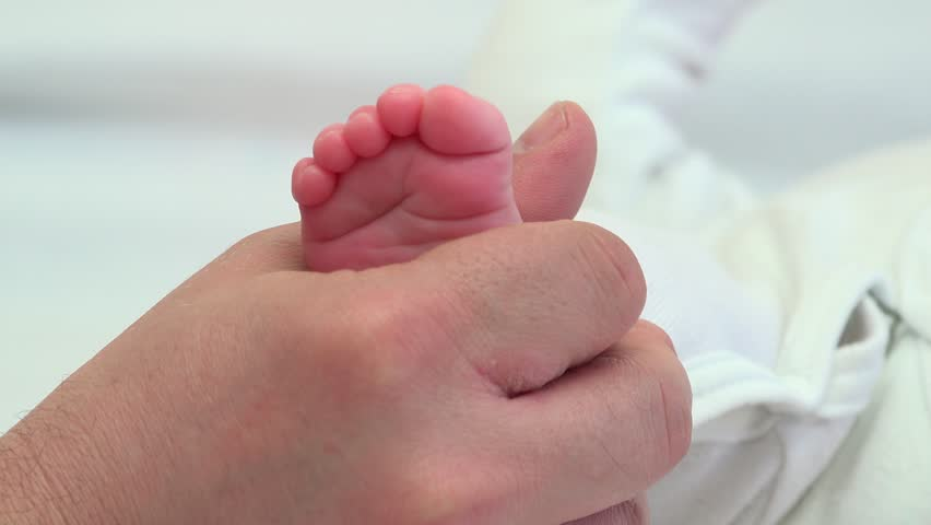 Young father kissing newborn leg, baby moving