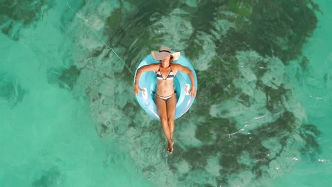 Aerial drone quad copter footage of woman floating on a lilo with hat in tropical waters of crystal clear waters of an ocean coral reef.