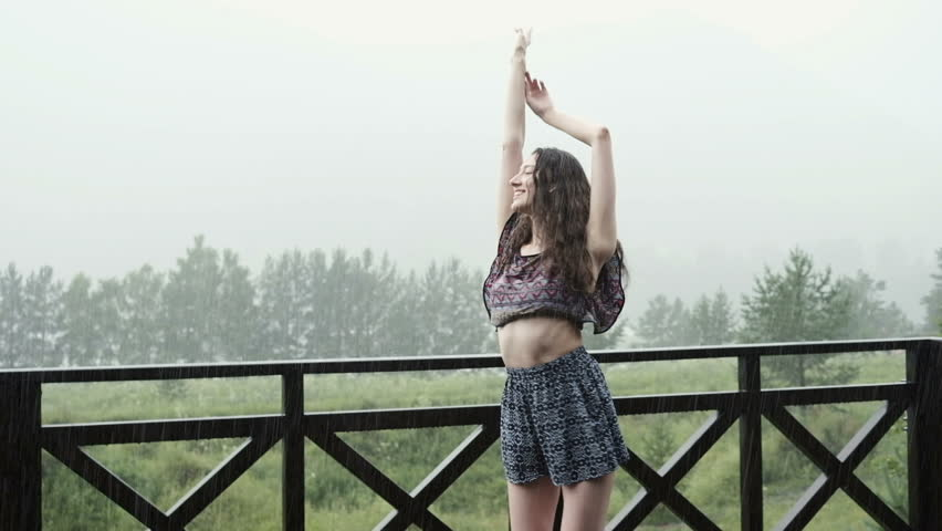 A happy woman smiles, listening to music and dancing in the rain. Happiness and freedom