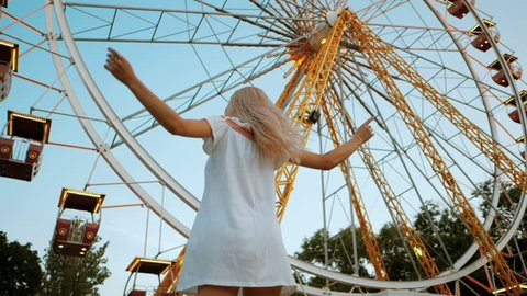 Young beautiful woman in short dress spinning standing against ferris wheel with colorful illumination. Slow motion. Girl have fun in amusement park at summer