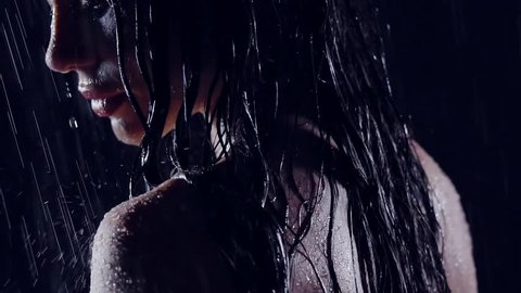 close-up portrait of a girl in the rain in the dark. in the face of flowing water. she was wet and naked