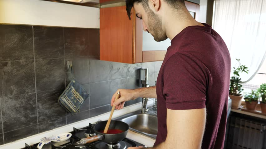 Man getting burn injury while cooking on kitchen at home.