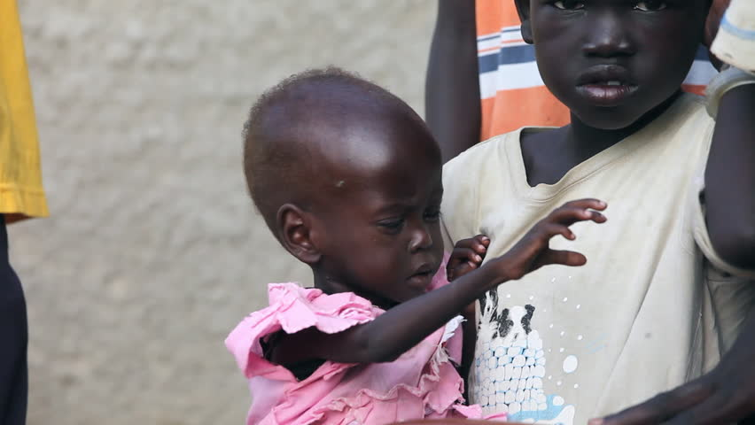 BOR, SOUTH SUDAN - JUNE 26, 2012: A starving child is held by her sister in war-torn South Sudan on June 26 2012. Conditions in South Sudan have worsened since independence from North Sudan.