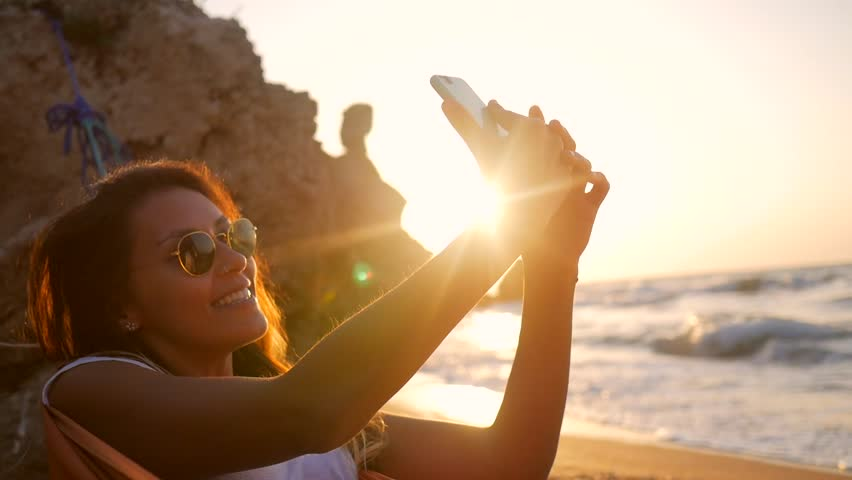 Young Mixed Race Girl Taking Selfie Photo while relaxing in hammock on the beach during amazing sunset. HD Slowmotion. | Shutterstock HD Video #29192905