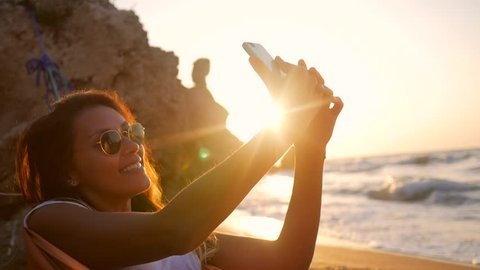 Young Mixed Race Girl Taking Selfie Photo while relaxing in hammock on the beach during amazing sunset. HD Slowmotion.