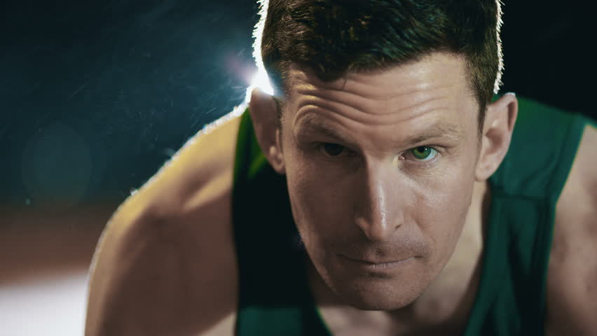 Close up on face of male runner at athletics track crouching at the starting blocks before a race. In slow motion.