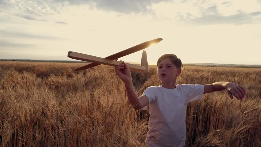 Happy child runs with a toy airplane on a sunset background over a wheat field | Shutterstock HD Video #29221465