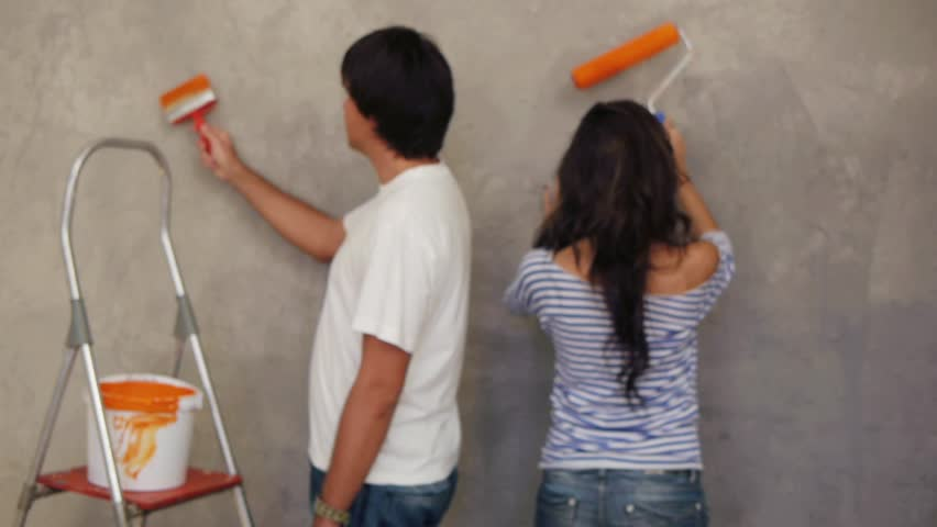 Attractive couple painting wall together
