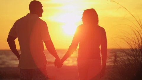 Silhouette of loving ethnic couple holding hands and enjoying sunset on beach vacation