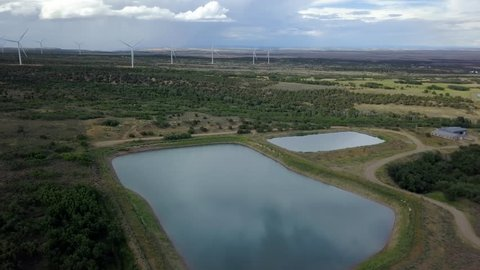 MONTICELLO, UTAH - 14 JUL 2017: Aerial rural community ponds windmill turbines electricity. Wind farm south eastern Utah. Important source of renewable energy by wind. Energy for homes and business.