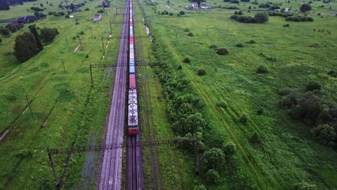 Rural landscape with the container train passing through countryside