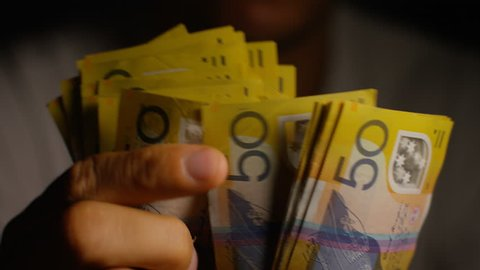 Male hands counting $50 notes in Australian dollars
