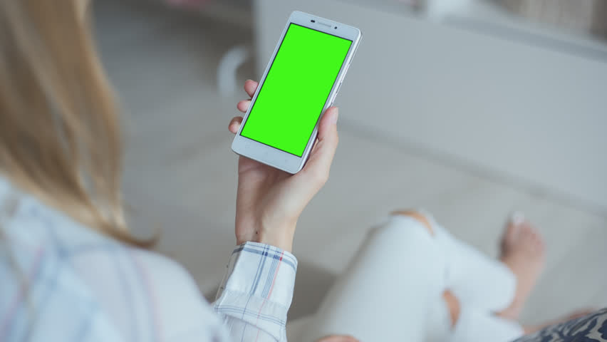 Young Woman in white jeans sitting on couch holds SmartPhone with pre-keyed green screen. Perfect for screen compositing. Made from 14bit RAW. 10bit ProRes 444 | Shutterstock HD Video #29241535