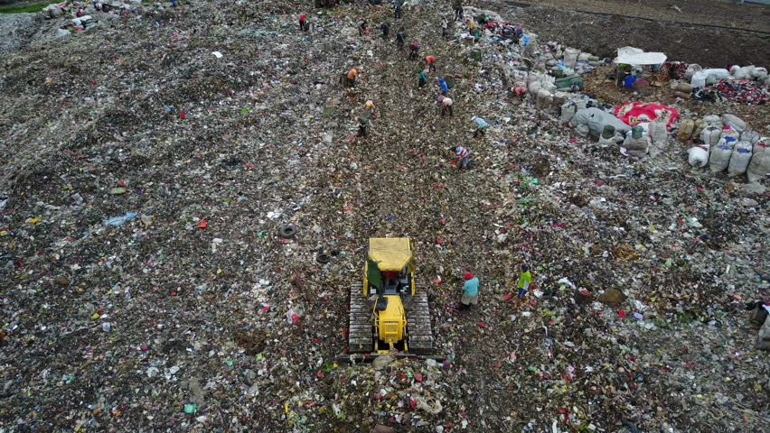 JAKARTA, INDONESIA - APRIL 2017: Frontal tracking aerial view of bulldozer pushing waste over massive garbage dump site in Jakarta, Indonesia