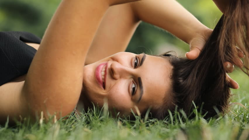 Attractive woman lying on grass at summertime, she relax and coquettish play with hair.