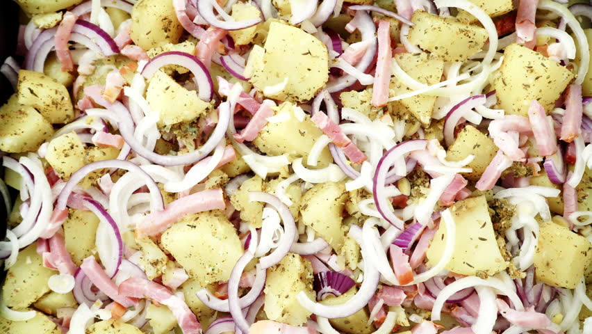Peeled potatoes with spices, bacon meat and onion slices ready to be roasted close up. Food background.