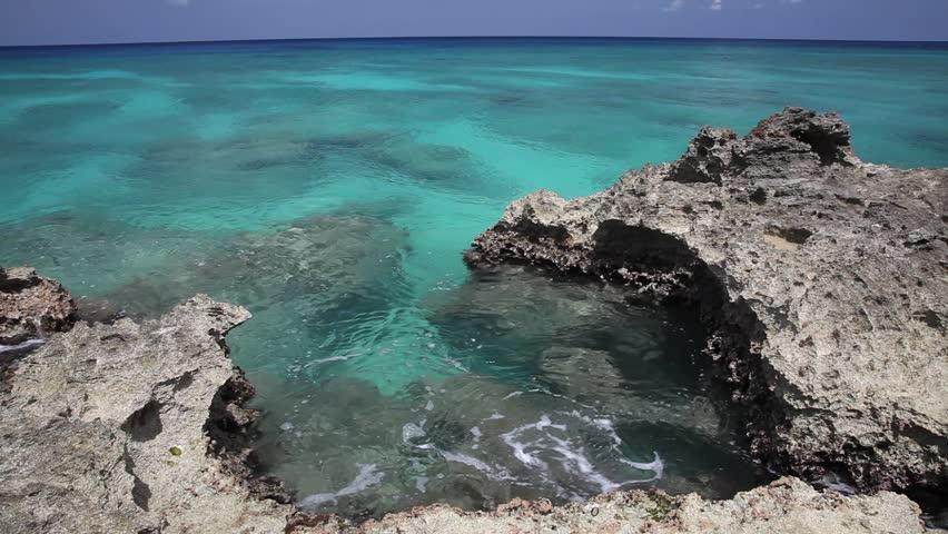 Gentle Caribbean sea waves touching rocks of Grand Cayman