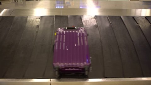 4k Baggage Claim in international airport. People picking up suitcase and Bags from conveyor belt at Taiwan. Luggage travels on a conveyor belt-Dan