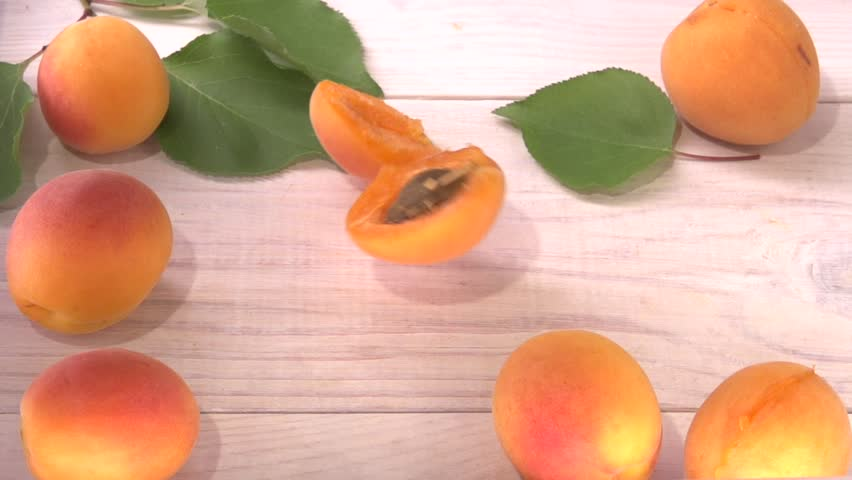 Apricot. Ripe Organic Apricots are rolling on the white wooden table. Slow motion 240 fps. Slowmo. High speed camera shot. Full HD 1080p.