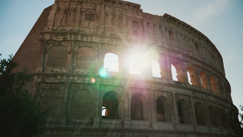 Arch of the famous Colosseum in Rome. The sun's rays shine through them. Steadicam shot