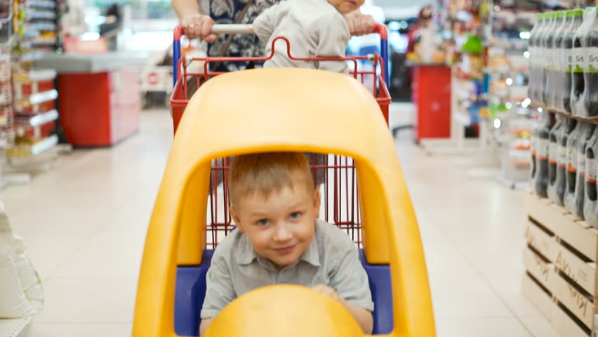 Two wonder active little kids in yellow plastic shopping-cart indoors casual marketplace with mummy. Modern beautiful mum slowly moving market-cart between products shelf and selection daily meal | Shutterstock HD Video #29322745