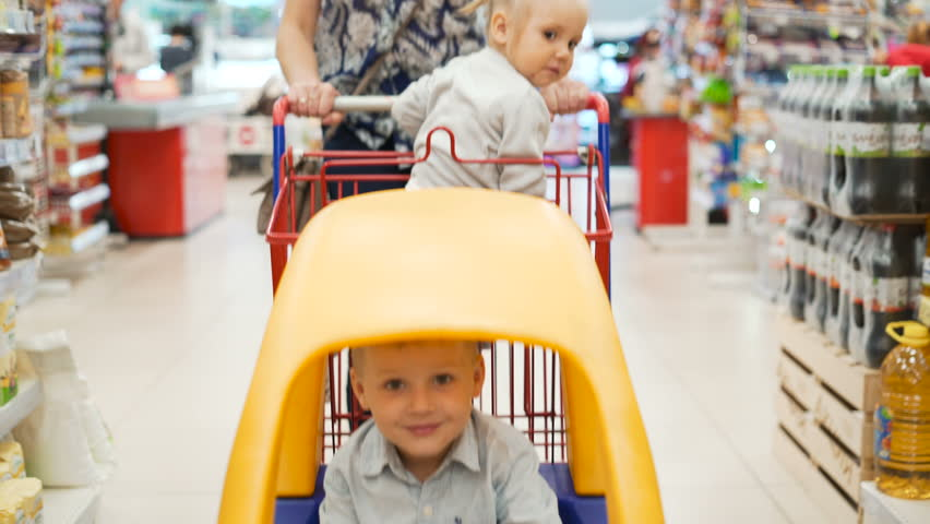 Two wonder active little kids in yellow plastic shopping-cart indoors casual marketplace with mummy. Modern beautiful mum slowly moving market-cart between products shelf and selection daily meal   Shutterstock HD Video #29322745