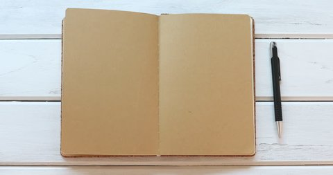 A male hand close diary book  on the white wooden desk, top view and overhead shot use for blank template book mock up to add any text content, 4K Dci resolution