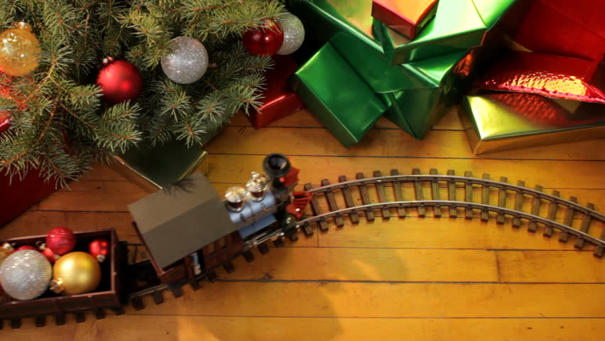 Toy electric train filled with christmas ornaments passes along wood floor on