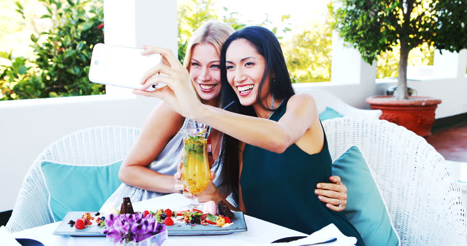 Friends having mocktail while taking selfie on mobile phone in resturant