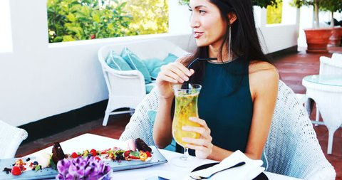 Beautiful woman drinking mocktail while having meal in resturant