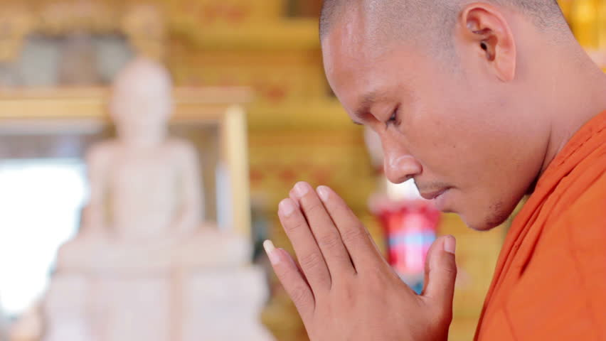 Closeup of Buddhist monk with orange robe pray in temple profile