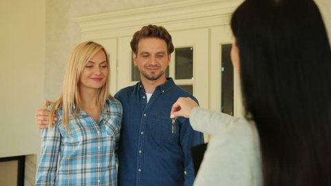 Young married couple getting a key to their new house from their realtor on the door of new house background.