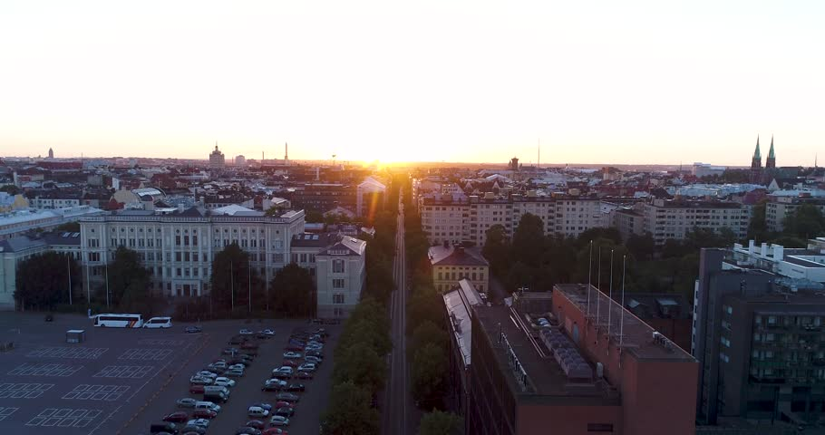 Aerial scenic view of Helsinki capital of Finland during sunrise. Drone rising above rooftops filming straight street line of Bulevardi ending at morning sun. Scandinavia