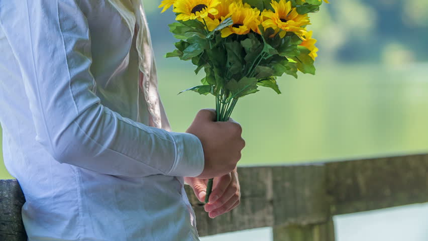 hd00:28A young man is holding a beautiful bouquet of sunflowers in ...