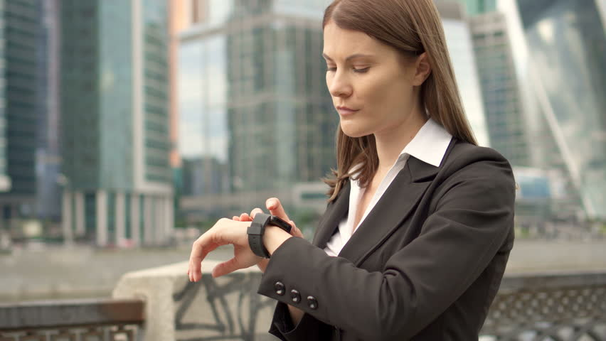 Young successful businesswoman in suit using smart watch in city downtown, professional female employer browsing chatting reading news. Business district skyscrapers in background | Shutterstock HD Video #29404975