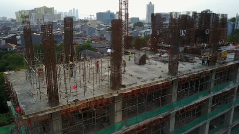JAKARTA, INDONESIA - APRIL 2017: Panning drone shot of busy construction site, development of new office tower in Jakarta, Indonesia
