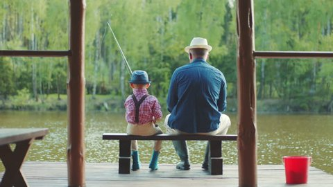 Old man and his grandson in straw hats are fishing on the river at summertime. They are holding rods in their hands