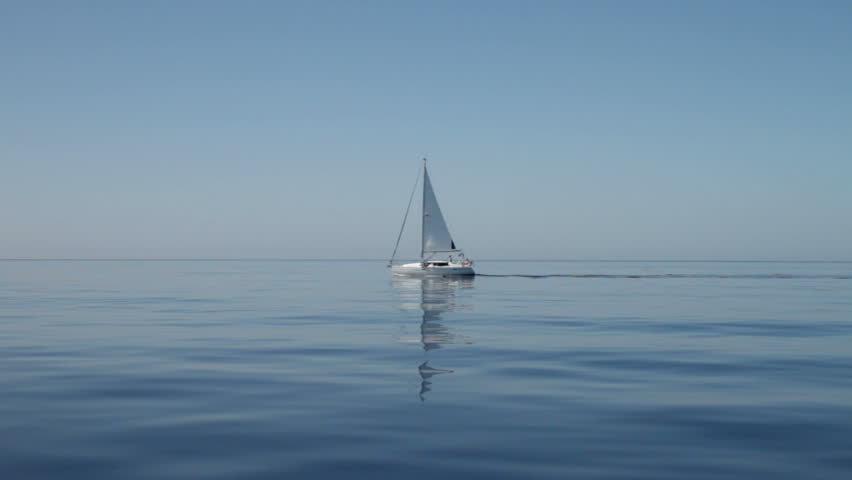 Yacht with reflection motor sails across calm still blue water in the Mediterranean on September 28, 2012 in the Ionian Islands.