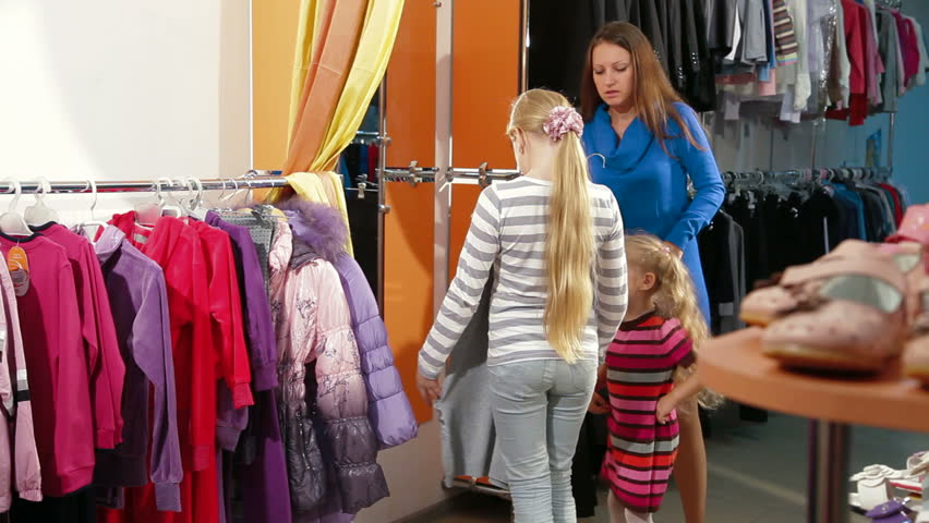Little Girl Shopping For Girls Clothes In A Clothing Store, Trying ...
