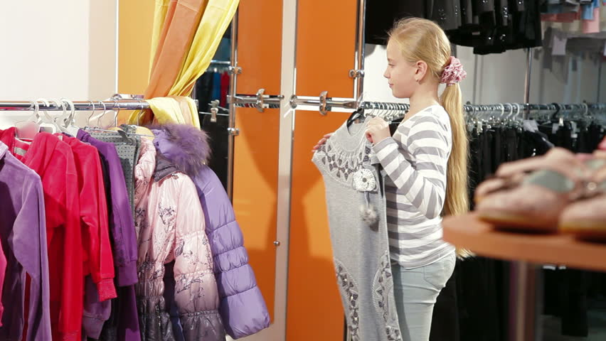 263d30f2024 Little girl shopping for girls clothes in a clothing store, trying on dress
