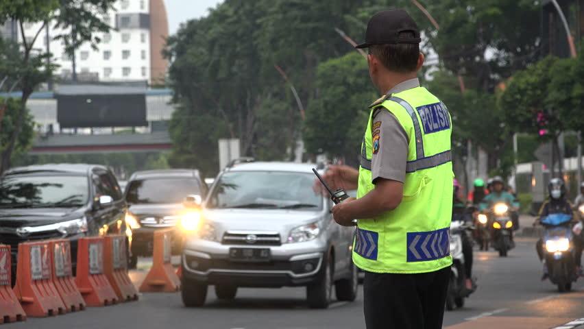 SURABAYA, INDONESIA - APRIL 2017: Indonesian police officer guides traffic during rush hour in Surabaya