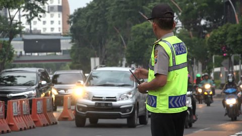 SURABAYA, INDONESIA - APRIL 2017: Indonesian police officer guides traffic during rush hour in Surabaya