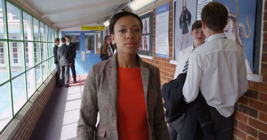 4K Strict teacher walking through school building & disciplining young teen students