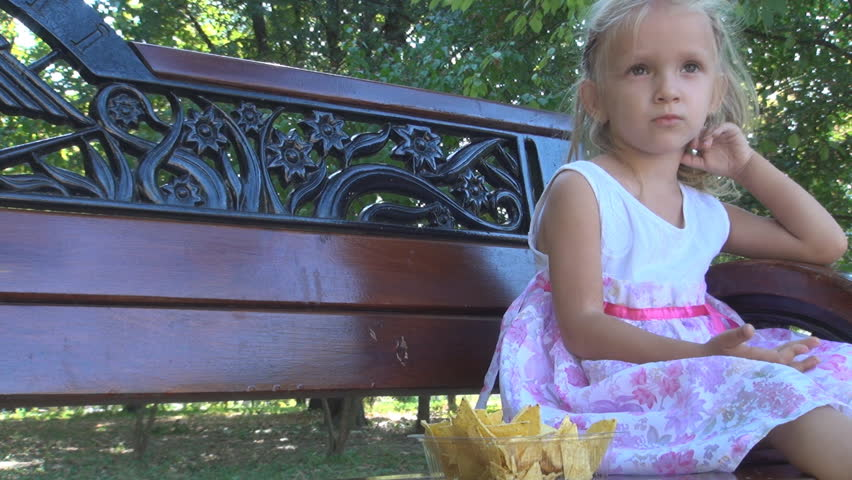 Little Girl Eating Cornflakes on a Bench in Park