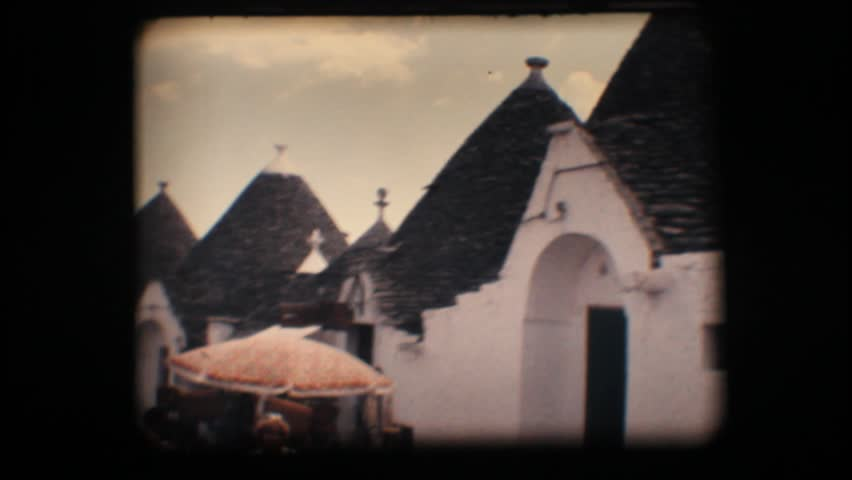 Vintage 8mm. Typical cone shaped houses (trullo) and tourists in Alberobello, a unique Italian town