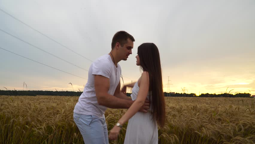 A guy with a girl in his arms is spinning in a wheat field at sunset. #29523955