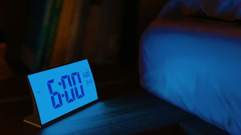 Digital alarm clock waking up at 6 AM. Close-up view. The clock screen is switching on for two seconds, then switching off for one second and go on. 3D rendering animation.