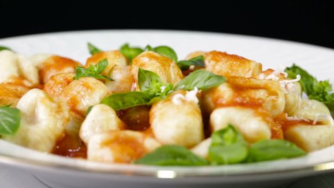 Italian food potato gnocchi in a white dish for a restaurant with grated cheese falling down.